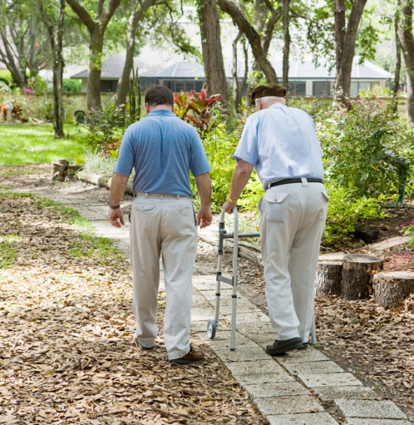 An elderly man walking, assisted by carer.