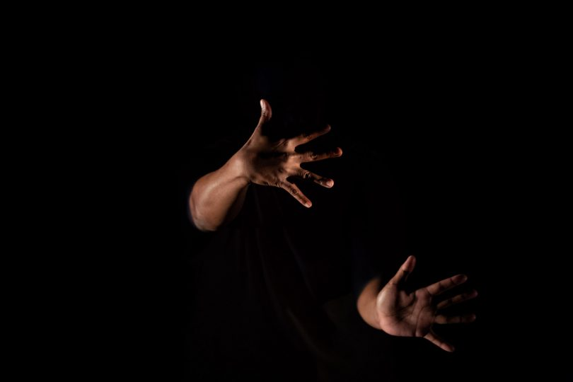 Photograph shows two hands emerging from darkness