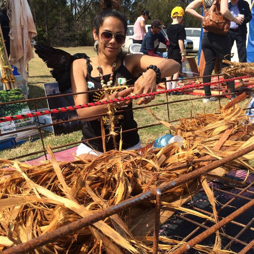 Narooma's Ashweeni Mason weaving stringy bark into a canoe sculpture. Photo: Giiyong Facebook.
