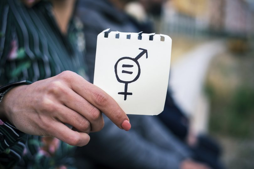 closeup of a young woman outdoors showing a piece of paper in front of her with a symbol for gender equality drawn in it.