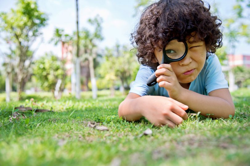 Little boy with magnifying glass in park.