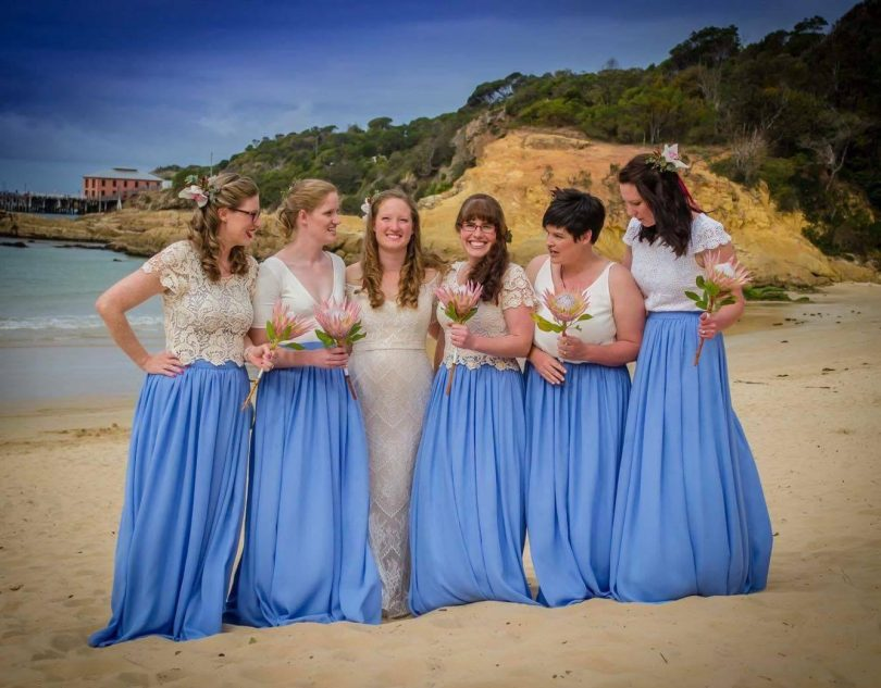 A bride and bridesmaids, dressed by CC Bridal in Pambula, on Tathra beach. Photo: Sapphire Coast Weddings and Events.