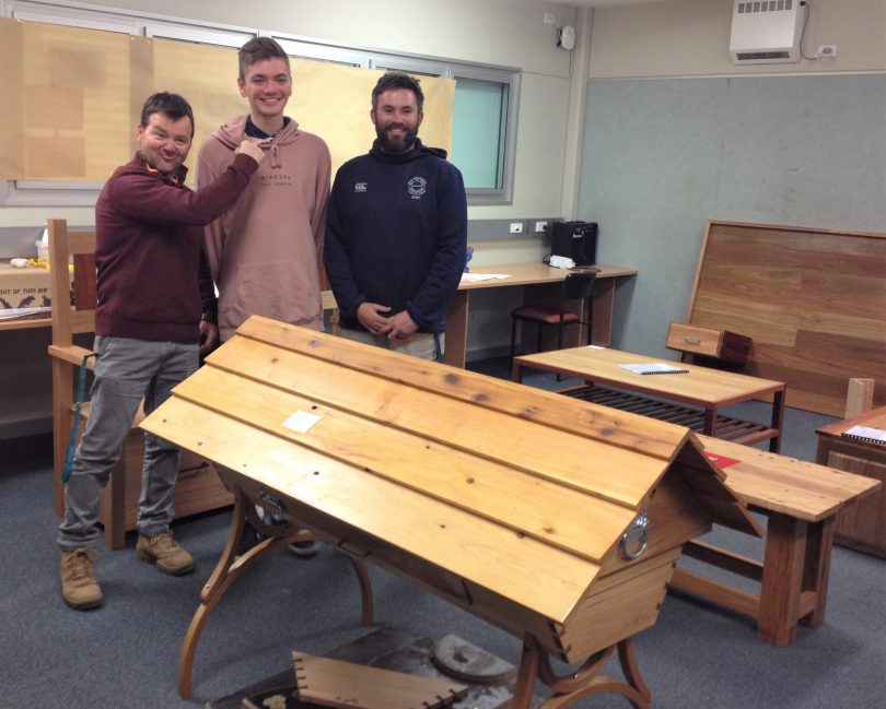 Student Eli Badger with the beehive he made and his woodworking teachers Mr Carrett [left] and Mr Collins [right]. Photo: Elka Wood.