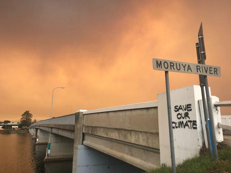 Bridge over Moruya River under orange sky from bushfires.