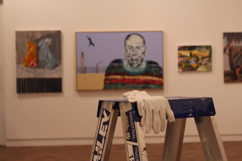 Ladder and gloves in foreground, hanging art in background at Goulburn Regional Art Gallery.