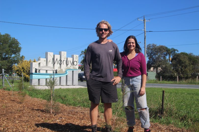Alex Chiswell and Eliza Cannon standing in front of Moruya town sign.