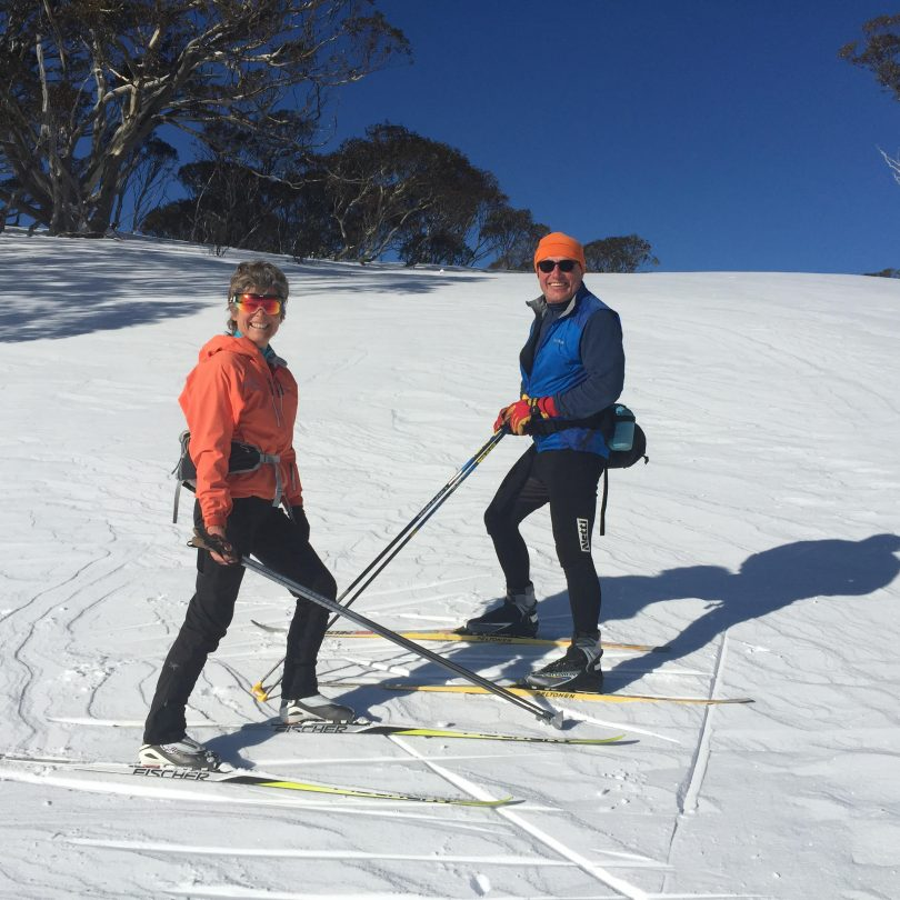 Acacia Rose (left) and Mike Edmondson (right) on standing on skis on snow.