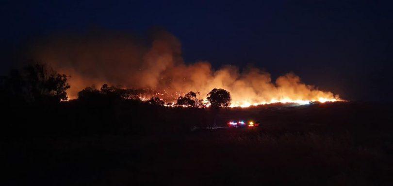 Bushfire burning in distance at night.