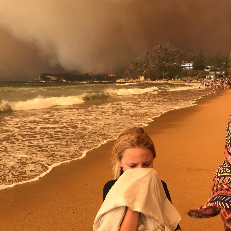 Girl covering face at Malua Bay beach with bushfire in background.