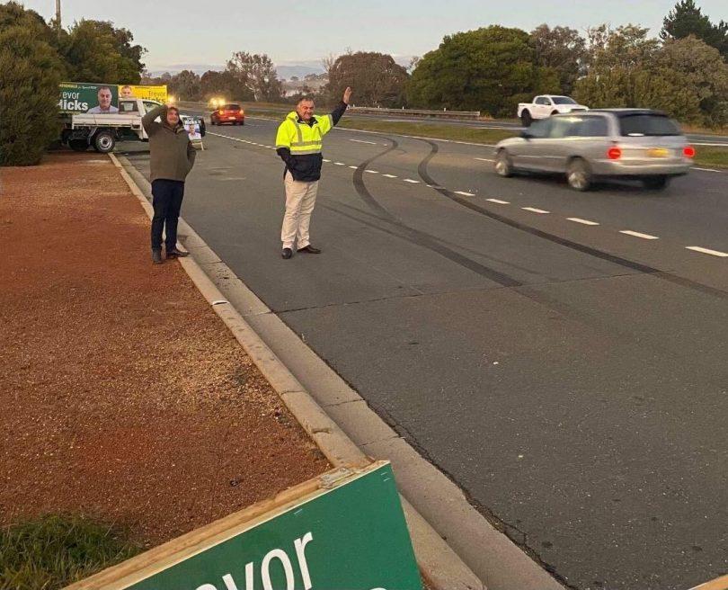 Trevor Hicks standing roadside waving to motorists.
