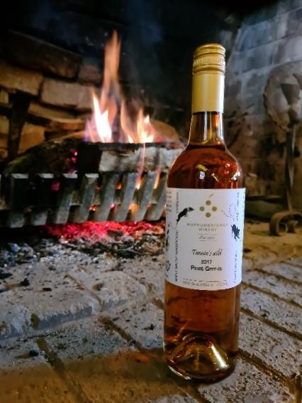 Bottle of wine from Murrumbateman Winery in front of fireplace.