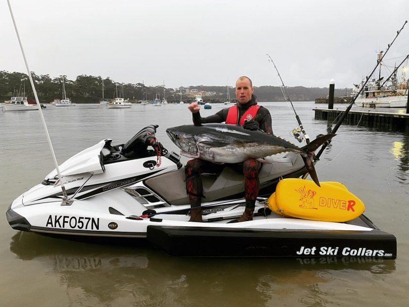 Spearfisherman Glen Thurston sitting on jet ski holding tuna.