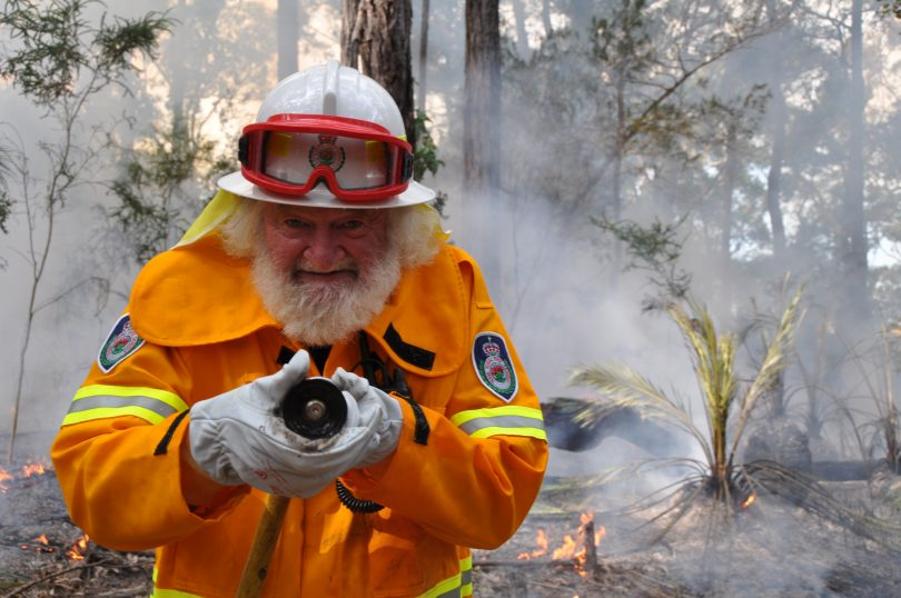 Terry McGee holding hose during bushfire.