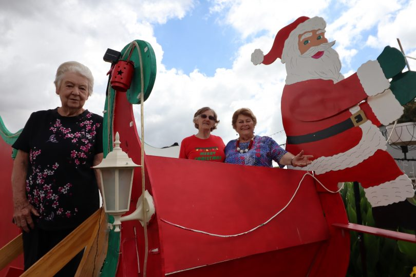 Freda Cook, Nancy Hook and Esma Drennan inside giant sleigh Christmas decoration.