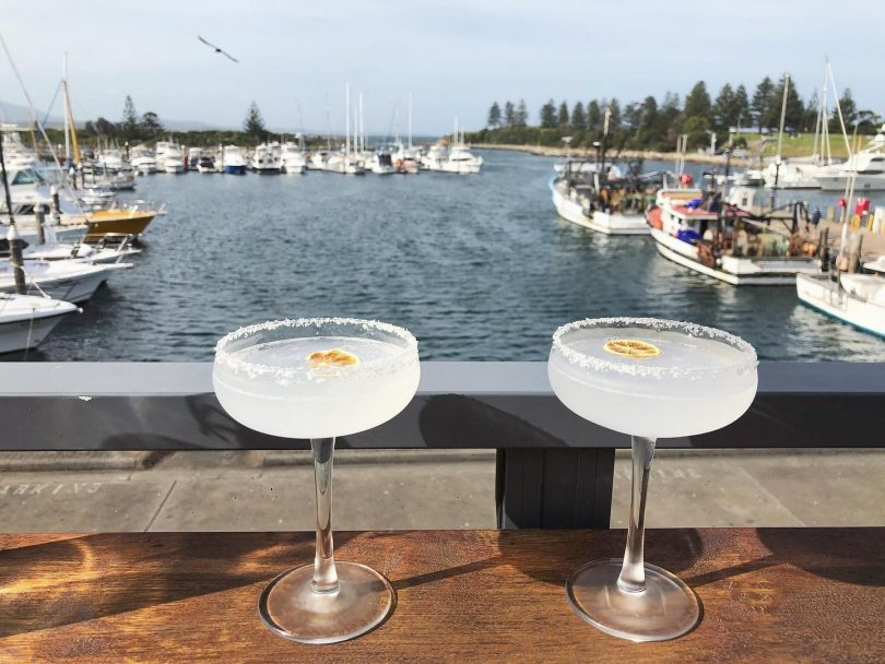 Two cocktails on bar in front of water in Bermagui.