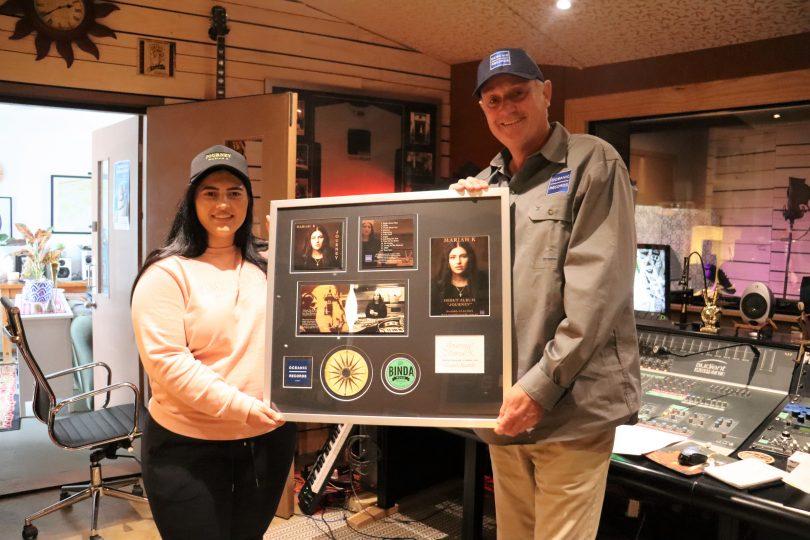 Mariah K and Stephen Lindsay holding framed album artwork in studio