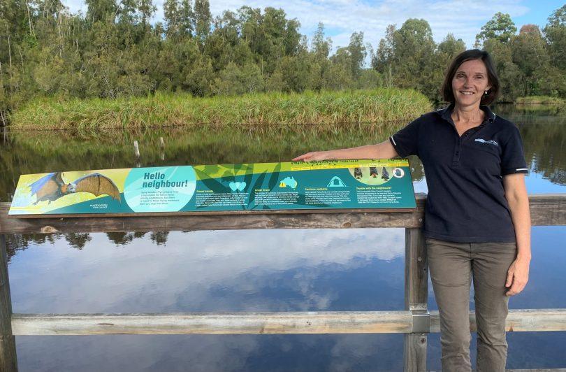 Natalie Foster standing next to educational sign at Batemans Bay Water Garden