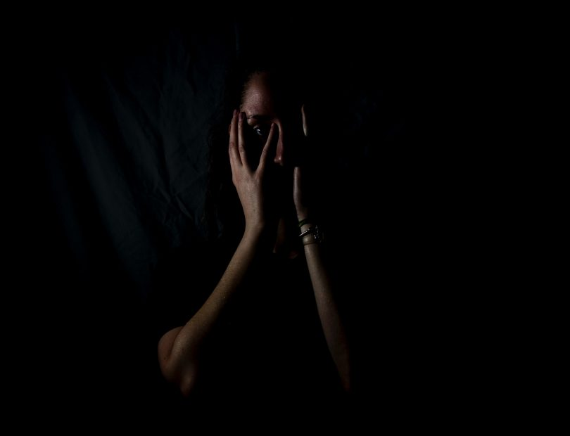 A scared woman covering her face with her hands