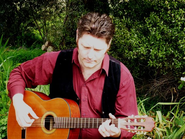 Daniel Kelly playing acoustic guitar outdoors