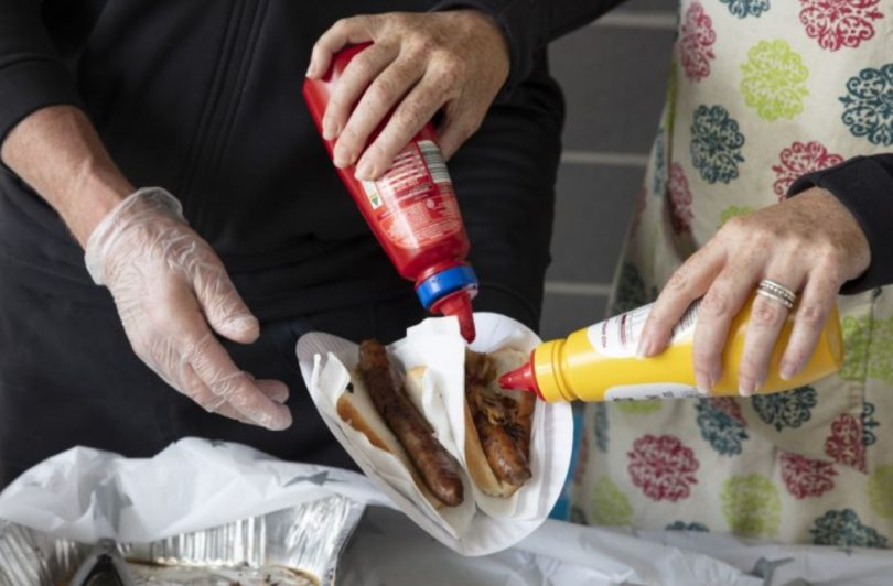Two people holding sauce bottles at sausage sizzle